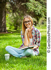 Studying on fresh air. Beautiful young female student holding hand on chin and smiling while sitting in a park