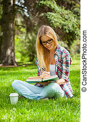 Studying outdoors. Confident young female student studying while sitting in a park