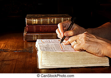 A man uses a pen to help him study an old and worn Holy Bible, while other versions and/or translations of the bible are nearby on the wood table.