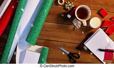 holidays, new year and christmas concept - snow falling over stuff for gifts wrapping on wooden table