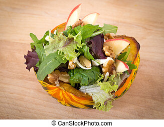stuffed carnival squash with apple nut salad over wood table...
