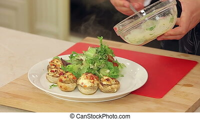 Stuffed champignon on white plate with salad