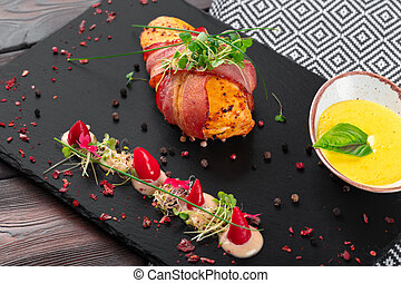 Stuffed chicken wrapped in bacon on a plate close-up
