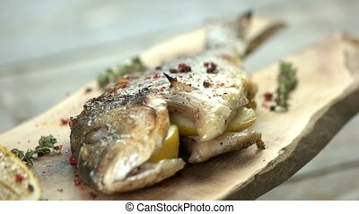 Stuffed dorado, lemon and herbs. Grilled fish with spices.