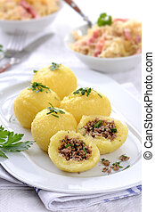 Potato dumplings stuffed with minced meat and served with sauerkraut and bacon