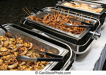 Stuffed mushrooms and skewered chicken sit in a buffet line.