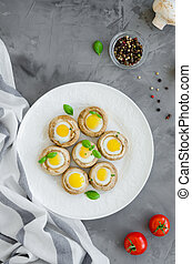 Stuffed mushrooms with quail eggs on a white plate with basil and thyme leaves on a dark concrete background. Easter appetizer. Vertical orientation. Top view.