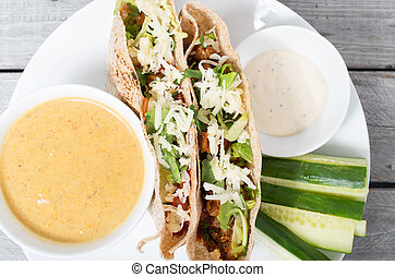 Stuffed pita with meat, cheese, vegetables and dipping sauce