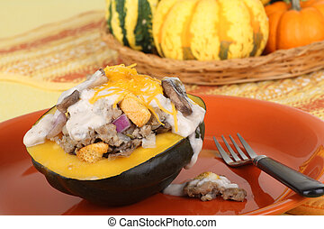 Baked stuffed acorn squash on an orange plate