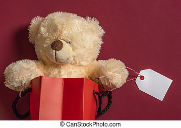 Stuffed teddy bear toy in a shopping bag with blank tag. Red background and copy space.