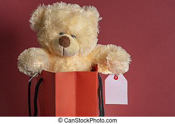 Stuffed toy in a shopping paper bag. Red background with copy space