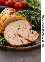 Stuffed turkey breast with baked vegetables and spices on a black background.