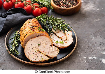 Stuffed turkey with baked vegetables and spices on a black background.
