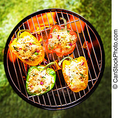 Stuffed veggy bell peppers grilling on a BBQ - View from...