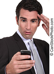 Stunned businessman reading a text message