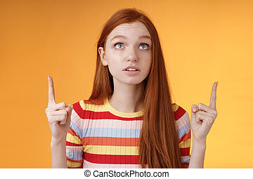 Stunned thrilled young redhead woman peer focused pointing up index fingers upwards look concentrated excited hold breath amused performance standing orange background intrigued and curious