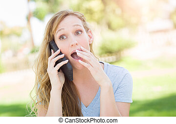 Stunned Young Woman Outdoors Talking on Her Smart Phone.