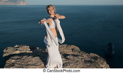 Stunner girl shows all the beauty of oriental dance standing on a mountain in Crimea