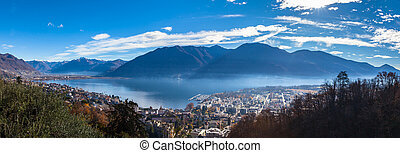 Stunning aerial panorama view of  Locarno cityscape and Lake Maggiore from Madonna del Sasso church, snow covered Swiss Alps mountain and blue sky cloud in background in autumn, Ticino, Switzerland