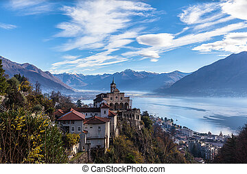 Stunning aerial panorama view of Madonna del Sasso church above Locarno city with Lake Maggiore, snow covered Swiss Alps mountain peaks and blue sky cloud in background in autumn, Ticino, Switzerland