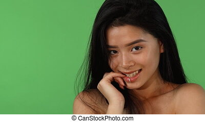 Stunning Asian woman biting her finger seductively smiling to the camera
