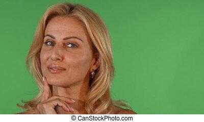 Stunning beautiful mature woman smiling looking thoughtfully...