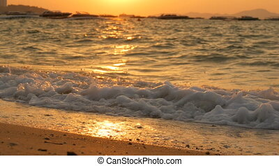 Stunning beauty of a red sunset on the beach. Waves with foam beat on sandy beach in Thailand