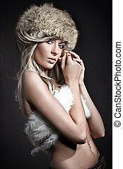 Stunning blonde beauty over dark studio background