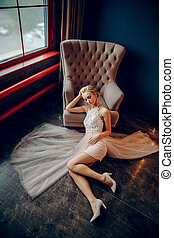 Stunning blonde props her head with her hand and reclines on the black floor next to a beige armchair