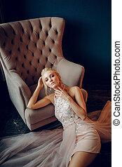 Stunning blonde touches her neck and reclines on the black floor next to a beige armchair