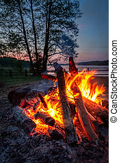Stunning bonfire at dusk by the lake in summer