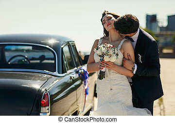 Stunning bride enjoys groom's kiss standing behind an old car in a windy weather