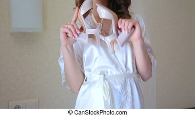 Stunning bride is playing with shoes