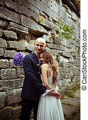 Stunning bride smiles being hugged by a groom
