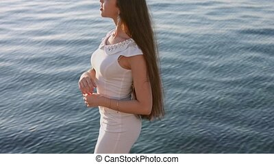 Stunning brunette with long hair dressed in the white tight dress standing by the sea