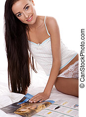 A stunning brunette woman wearing lingerie and reading a fashion magazine, seated on bed, white studio background