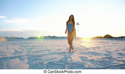 Stunning brunette woman with long hair dances in the evening lights on the beach
