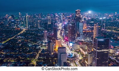 Stunning City View of Futuristic Skyline at Night, Skyscrapers in Asian Indonesian Capital Jakarta with flashing lights and Car Traffic Flow on Main road, Aerial Hyperlapse Time Lapse, Drone View