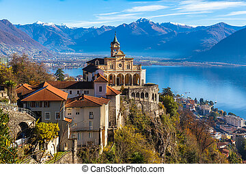 Stunning close up panorama view of Madonna del Sasso church above Locarno city with Lake Maggiore, snow covered Swiss Alps mountain peak and blue sky cloud in background in autumn, Ticino, Switzerland