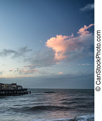 Stunning colorful Winter sunset sky above burned out pier at sea