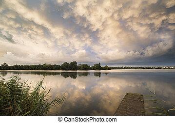 Stunning dramatic mammatus clouds formation over lake...