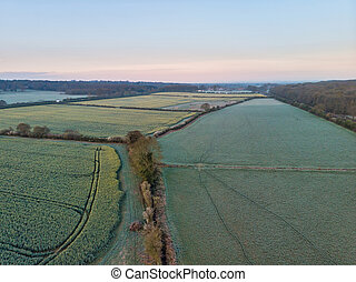 Stunning drone aerial landscape image of Englsh countryside at sunrise in Spring over rapeseed canola fields