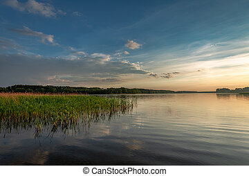 Stunning dusk at the summer lake with dynamic clouds