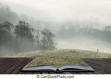 Stunning foggy English rural landscape at sunrise in Winter with layers rolling through the fields coming out of pages in magical story book