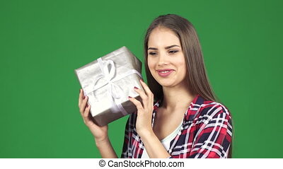 Stunning happy young woman shaking present box guessing what...