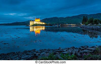 Stunning illuminated Eilean Donan Castle at dusk in Scotland