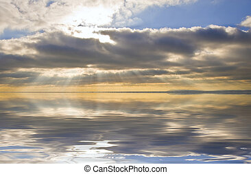 Stunning inspirational sunset image with glowing sun beams reflected in smooth simulated water