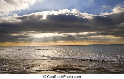 Stunning inspirational sunset image with glowing sun beams