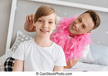 Stunning joyful lady getting her hair done by dad