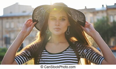 Stunning lady with long hair and black hat walks along the...